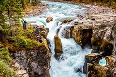 Deux personnes regardant Sunwapta Falls en Jasper National Park Photographie stock