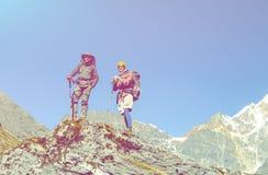 Deux personnes restant sur la haute roche en montagnes donnant sur le paysage Images stock