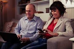 Deux personnes rident sur le sofa regardant des dispositifs Photographie stock