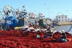 Deux personnes s'asseyant au milieu de Th des filets de pêche rouges ont écarté sur la terre et les filets de couture Images libres de droits