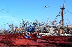 Deux personnes s'asseyant au milieu de Th des filets de pêche rouges ont écarté sur la terre et les filets de couture Image stock