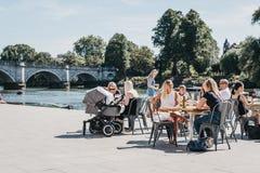 Deux personnes s'asseyant et détendant aux tables extérieures par la rivière T images libres de droits