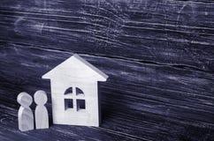 Deux personnes se tiennent près de la maison Figures en bois Image libre de droits