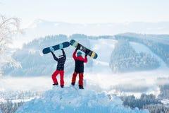 Deux personnes se tiennent sur la congère et soulèvent leurs surfs des neiges  Photos libres de droits