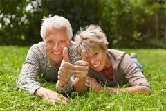Deux personnes supérieures tenant des pouces  Photo stock