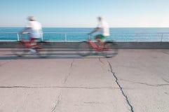 Deux personnes sur des bicyclettes dans le mouvement. Photographie stock