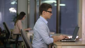 Deux personnes travaillant à l'ordinateur portable dans le grand bureau, support technique, centre de service banque de vidéos