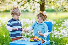 Deux petit ami dans des oreilles de lapin de Pâques colorant des oeufs Photographie stock libre de droits