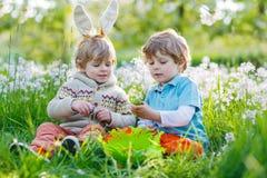 Deux petit ami dans des oreilles de lapin de Pâques pendant l'oeuf chassent Images stock