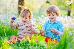 Deux petit ami dans des oreilles de lapin de Pâques pendant l'oeuf chassent Photo libre de droits
