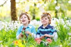 Deux petit ami dans des oreilles de lapin de Pâques mangeant du chocolat Image libre de droits