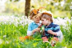 Deux petit ami dans des oreilles de lapin de Pâques mangeant du chocolat Photo stock