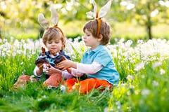 Deux petit ami dans des oreilles de lapin de Pâques mangeant des gâteaux et des petits pains de chocolat Photos libres de droits