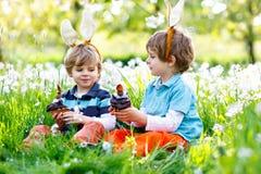 Deux petit ami dans des oreilles de lapin de Pâques mangeant des gâteaux et des petits pains de chocolat Photographie stock