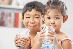 Deux petite fille et garçon chaque glace de fixation de lait Image stock