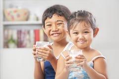 Deux petite fille et garçon chaque glace de fixation de lait Photographie stock