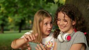 Deux petites ?coli?res ? l'aide du smartphone Enfants jouant, lecture, regardant le t?l?phone Les gens, enfants, technologie banque de vidéos