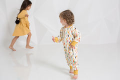 Deux petites filles élégantes courent après l'un l'autre sur le fond blanc de mur Photo stock
