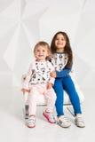 Deux petites filles élégantes s'asseyent sur une chaise ronde sur le fond blanc de mur Photo libre de droits