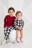 Deux petites filles élégantes s'asseyent sur une chaise ronde sur le fond blanc de mur Photographie stock libre de droits