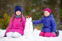Deux petites filles adorables construisant un bonhomme de neige ensemble dans le beau parc d'hiver Soeurs mignonnes jouant dans u Photographie stock libre de droits