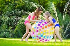 Deux petites filles adorables jouant avec du ballon de plage gonflable dans une arrière-cour le jour ensoleillé d'été Enfants mig Photographie stock