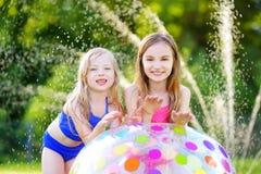 Deux petites filles adorables jouant avec du ballon de plage gonflable dans une arrière-cour le jour ensoleillé d'été Enfants mig Photographie stock libre de droits