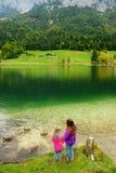 Deux petites filles appréciant la vue des eaux vertes merveilleuses du lac Hintersee Paysage étonnant d'automne des Alpes bavaroi images stock