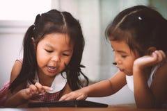 Deux petites filles asiatiques ayant l'amusement à observer sur le comprimé ensemble images stock