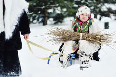 Deux petites filles avec des manteaux de fourrure et des châles dans le style russe sont portées sur une bracée de traîneau de br photo stock