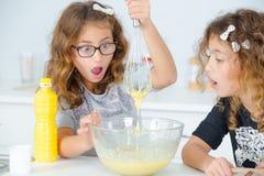 Deux petites filles ayant la cuisson d'amusement photographie stock libre de droits