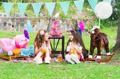 Deux petites filles buvant du jus dans un flacon cristal à se reposer dehors dans un jardin sur le pastel de port ensoleillé de j Photographie stock