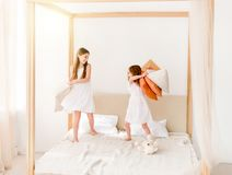 Deux petites filles combattant avec des oreillers sur le lit Photos stock
