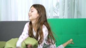Deux petites filles combattant avec des oreillers sur le sofa banque de vidéos