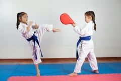 Deux petites filles démontrent des arts martiaux fonctionnant ensemble photos stock