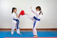 Deux petites filles démontrent des arts martiaux fonctionnant ensemble image libre de droits