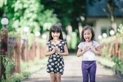 Deux petites filles détendant le jeu en parc et mangent des lucettes Photographie stock