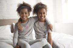 Deux petites filles d'afro-américain sur le lit à la maison photos libres de droits
