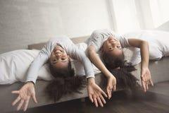 Deux petites filles d'afro-américain sur le lit à la maison photographie stock libre de droits