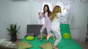 Deux petites filles dans des pyjamas dansant sur le sofa banque de vidéos