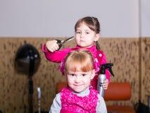 Deux petites filles dans le raseur-coiffeur Photo stock