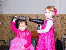 Deux petites filles dans le raseur-coiffeur Photo libre de droits