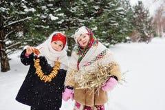 Deux petites filles dans les manteaux de fourrure et des châles dans le style russe sur le sien photos stock