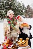 Deux petites filles dans les manteaux de fourrure et des châles dans le style russe sur le sien image libre de droits