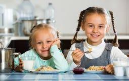 Deux petites filles de sourire mangeant la farine d'avoine saine Photos libres de droits