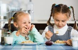 Deux petites filles de sourire mangeant la farine d'avoine saine Image libre de droits