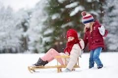 Deux petites filles drôles ayant l'amusement avec une dextérité dans le beau parc d'hiver Enfants mignons jouant dans une neige Photo libre de droits