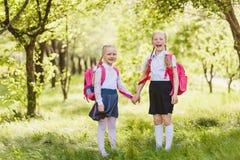 Deux petites filles drôles d'écolières se tiennent avec des sacs à dos et tiennent des mains en plein air photo libre de droits