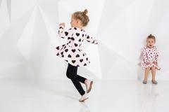 Deux petites filles drôles et riantes dans doucement le rose habillent jouer dans le studio blanc Photo libre de droits