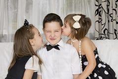 Deux petites filles embrassent le beau garçon Images stock